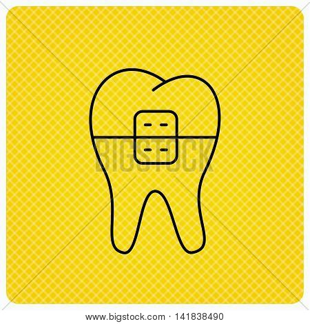 Dental braces icon. Tooth healthcare sign. Orthodontic symbol. Linear icon on orange background. Vector
