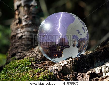 Ball Sphere in the woods on moss. Reflection - the city the lightning in the sky. The concept of security tranquility natural disaster