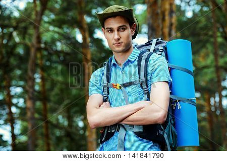 Adventure concept. Young man hiking in the forest. Active lifestyle, tourism. Tourist equipment.
