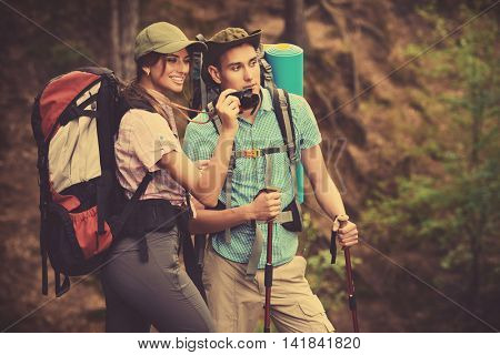 Hiking couple. Young people makes a hike in the woods. They take pictures of nature. Active lifestyle, tourism. Tourist equipment.