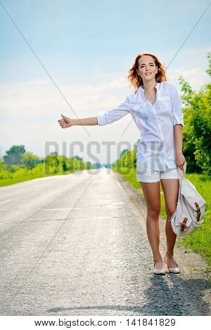 Hitchhiking girl. Attractive young woman standing on a highway and catching a passing car.