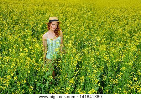 Romantic girl standing on a yellow meadow on a sunny summer day. Smiling young woman outdoor. Holidays, summer vacation.