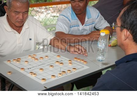 Palau Ketam, Malaysia - October 10, 2013; Men playing Chinese Chess passing the time of day with focus on the game pieces small Malaysian village.