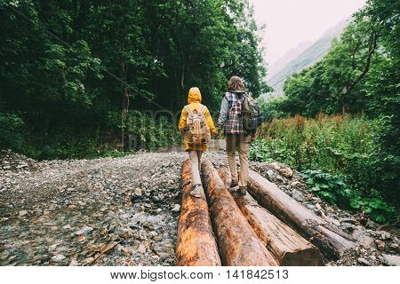 Hikers with backpacks walking in the forest, father with child, rain weather
