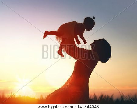 Happy loving family. Mother and her daughter baby girl playing and laughing in the summer at sunset outdoors.