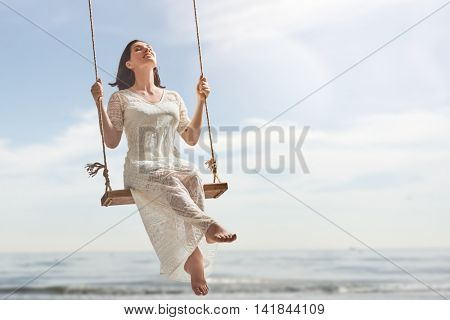 beautiful young woman on a swing on summer day outdoors