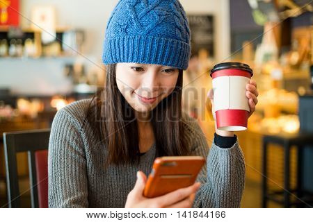Woman using mobile phone inside cafe