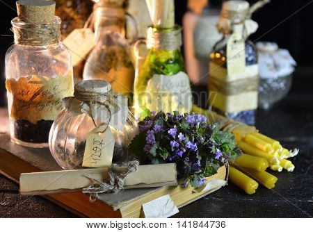 Magic still life with witch bottles and healing herbs. Halloween or homeopathic image. Signs on labels are not foreign text, these letters are imaginary, fictional symbols.