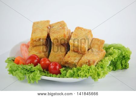 Fried tofu with lettuce tomatoes and carrot on white plate