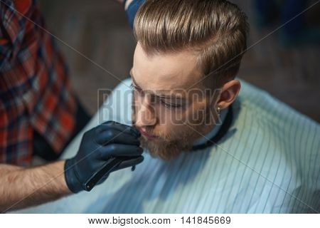 Young bearded man in a barber shop
