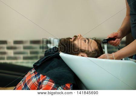 Male washing head in a barber shop