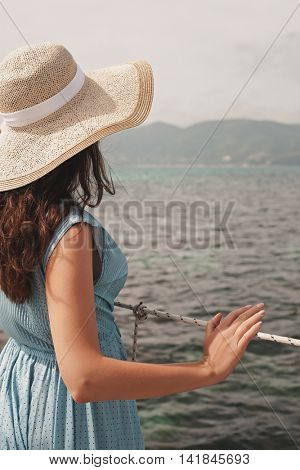 Young woman in summer dress standing on bridge and holding straw hat looking to sea
