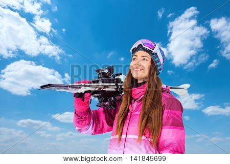 Smiling woman with skis outdoors