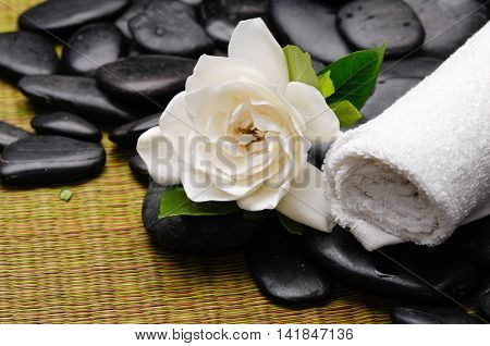 towel and stones and gardenia on bamboo mat