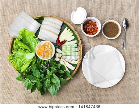 Vietnamese steamed thin rice pancake for pork rolls or banh uot Hue with lettuce herbs and chili sauces