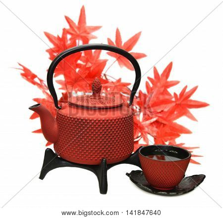 Red metal tea pot and cup with tea against background of maple leaves, isolated objects