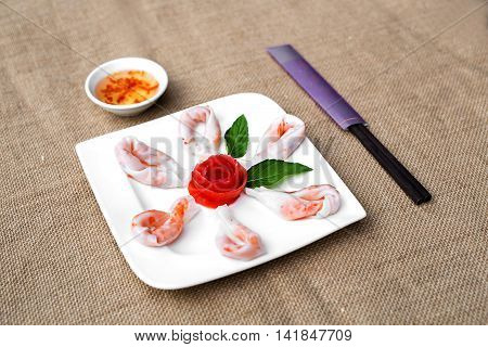 Vietnamese steamed thin rice pancake for fried shrimp rolls or banh uot Hue with lettuce herbs and chili sauces
