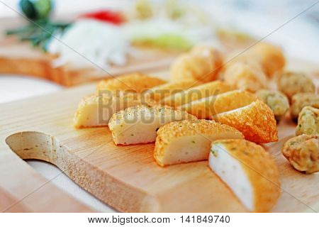 Sliced fish cake laksa on wooden cutting board in kitchen