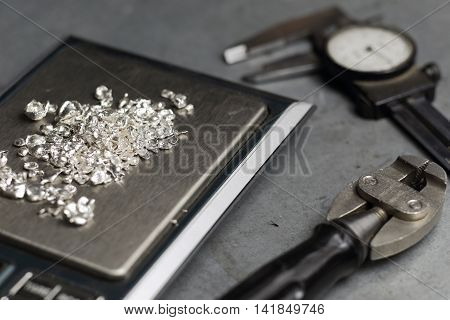 Tools Of Jewellery. Jewelry Workplace On Metal Background. Weigh-scales With Granules Of Silver.