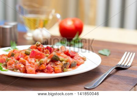 Fresh vegetable stew on wooden background with salt pepper and oil