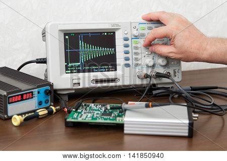 The man's hand turning signal adjustment knob on the oscilloscope panel