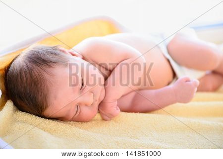 After childbirth newborn baby sleeping in a bed with a diaper poster