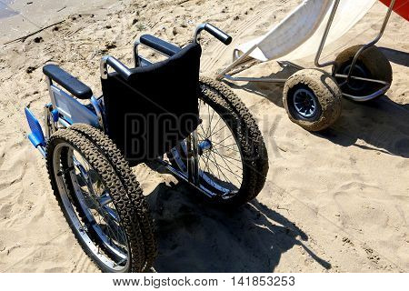 Two Wheelchairs On The Sand Of The Beach