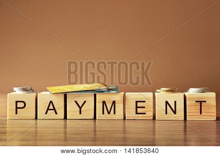 Wooden cubes with word Payment, credit cards and coins on   table
