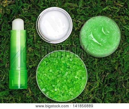 Cosmetics for lip skin care: sea salt, natural honey scrub with essential oils, lip cream and balm on green moss