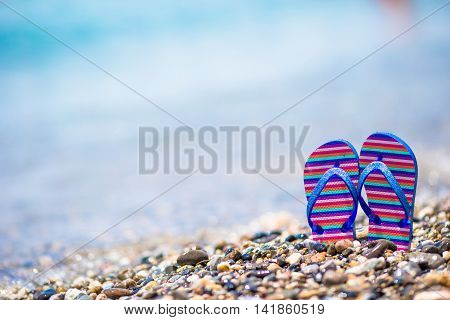 Kids flip flop on beach in front of the blue sea