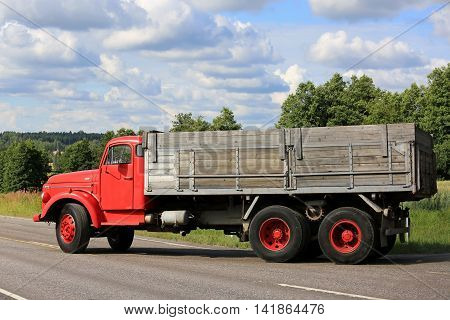 TENHOLA, FINLAND - JULY 30, 2016: Side view of red conventional Volvo N86 truck which turns right to enter the main road on a beautiful day of summer in South of Finland.