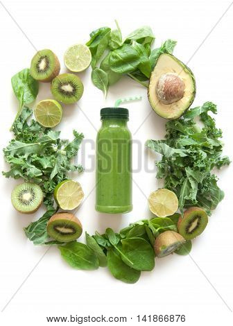 Bottled green smoothie surrounded with fruits and vegetables including spinach kale and avocado