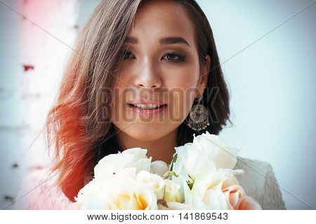 Pin-up girl in a white dress with flowers. professional model