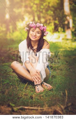 Beautiful young brunette woman in boho style outfit, with pink roses flower crown sitting outdoors in nature in park on sunny summer day. Matte filter applied, colorful photo, natural light.