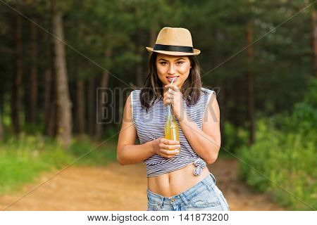 Young cheerful brunette woman in striped crop to and straw fedora hat, drinking lemonade from the bottle with straw, standing outdoors in park. Vibrant colors, natural light, medium retouch.
