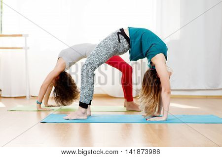 Two flexible young women practice chakrasana asana in yoga studio, backbend pose