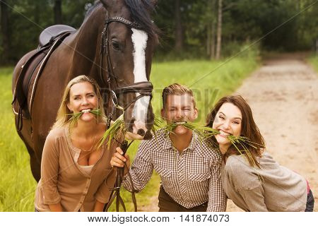 two woman and one man with horse and all pretending to eat grass