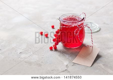 Homemade red currant jam or syrup on a stone background. Closeup horizontal with copy space