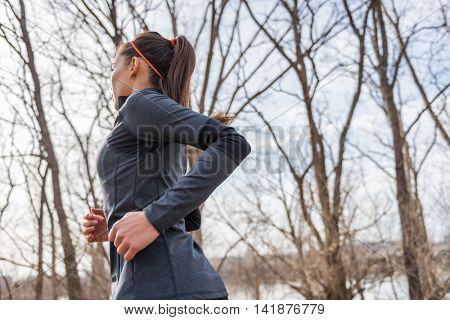 Young fitness woman runner running on trail. Girl athlete working out cardio in autumn or winter nature outdoors on forest trail in sunlight fall wearing cold weather jacket.