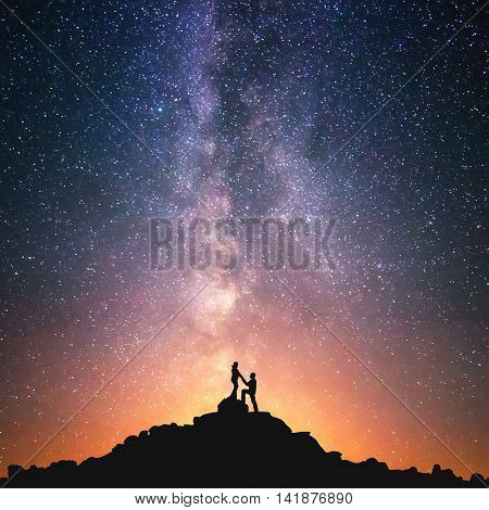 Romantic couple standing together holding hands in the mountains. Beautiful Milky Way galaxy on the background. poster