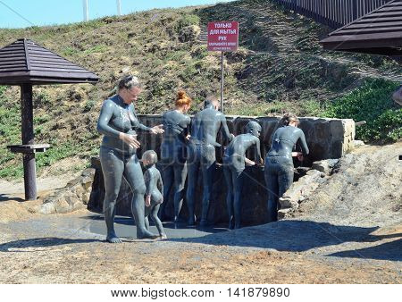 TEMRYUK DISTRICT, RUSSIA - AUGUST 29, 2015: Unidentified holidaymakers are washed with fresh water  after swimming in mud volcano Tizdar on Azov Sea
