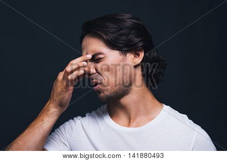 Feeling that unpleasant smell. Portrait of young man keeping eyes closed and expressing disgust while touching nose by fingers and standing against grey background