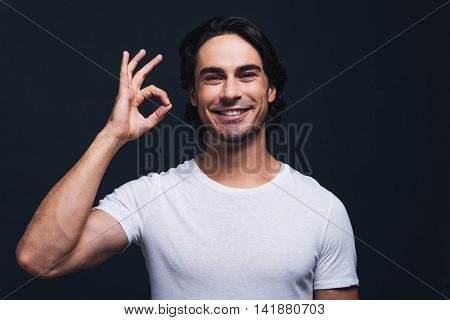 Everything is OK. Happy young man gesturing OK sign and looking at camera while standing against grey background