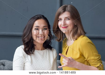 front view of two smiling young female friends sitting in the living room at home. 2016