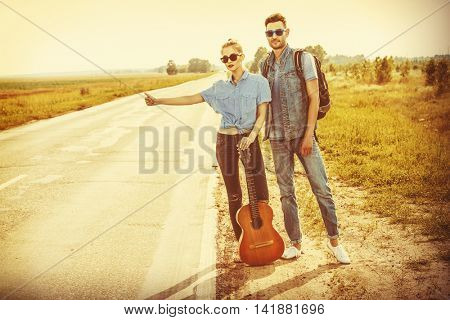 Hitchhiking couple. Romantic young people standing on a highway and catching a passing car.