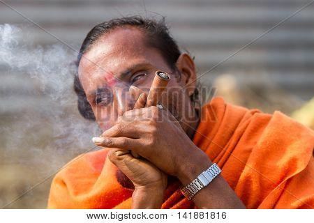 ALLAHABAD INDIA - FEB 13 - A Hindu sadhu smokes a hash pipe during the festival of Kumbha Mela on February 13th 2013 at Allahabad India.