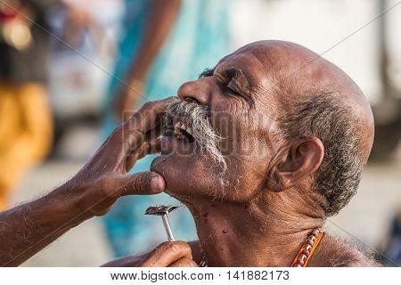 Pilgrim Getting A Rough Shave At The Kumbha Mela, India.