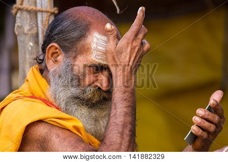 ALLAHABAD, INDIA - FEB 14 - A Hindu pilgrim applies tilak on his forehead during the festival of Kumbha Mela on February 14th 2013 at Allahabad, India.