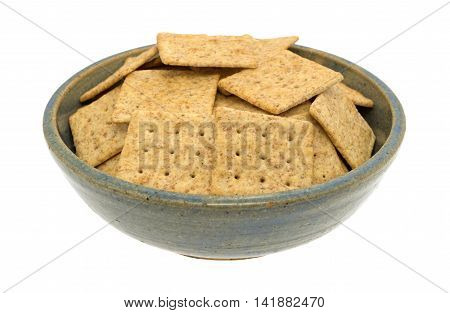 A bowl full of an organic whole wheat crackers isolated on a white background.