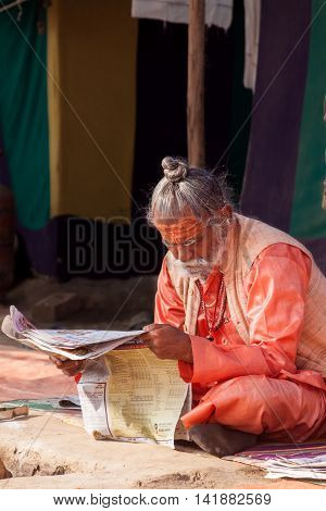 ALLAHABAD, INDIA - FEB 13 - A Hindu priest studies scriptures in front of his tent during the festival of Kumbha Mela on February 13th 2013 at Allahabad, India.